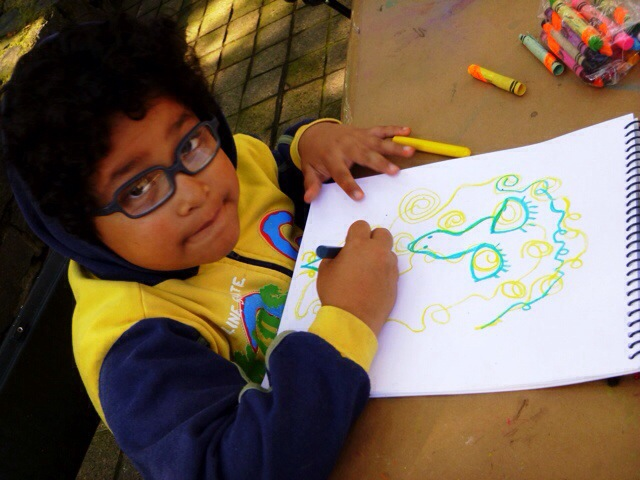 Alberto, age 7, uses crayons for his art.