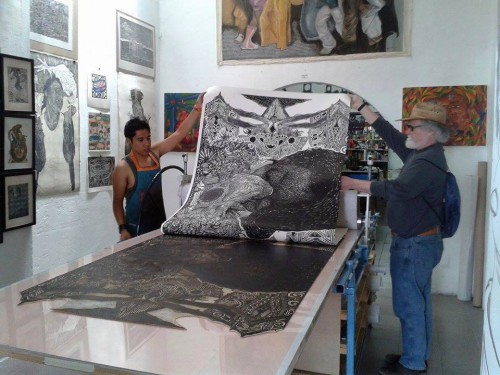 Alan Altamarino  on press pulling a large scale print with Kevin McCloskey