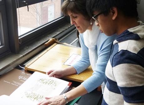 Cheryl Sheeler showing her portfolio to senior Arren Dawinan.