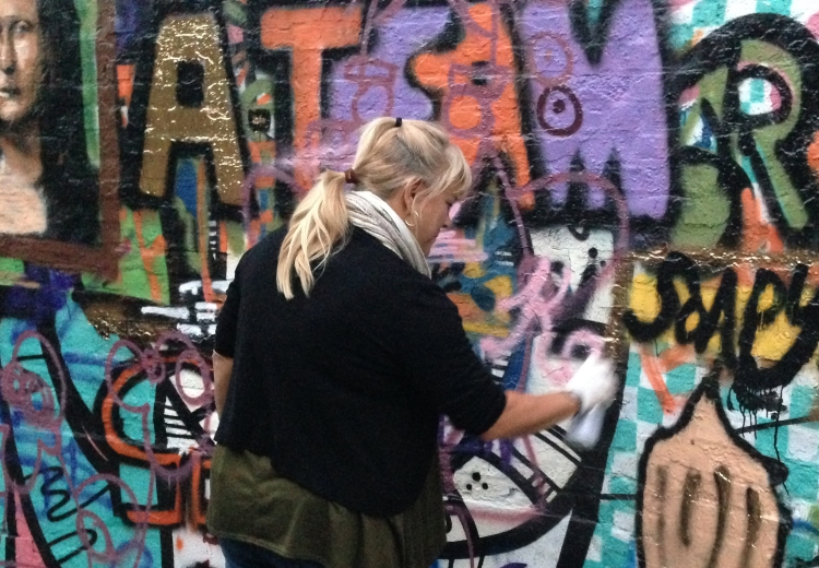 Kathy Sue Traylor tagging the wall in graffiti alley.