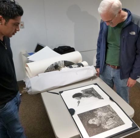 Evan Summer admire a portfolio etchings.